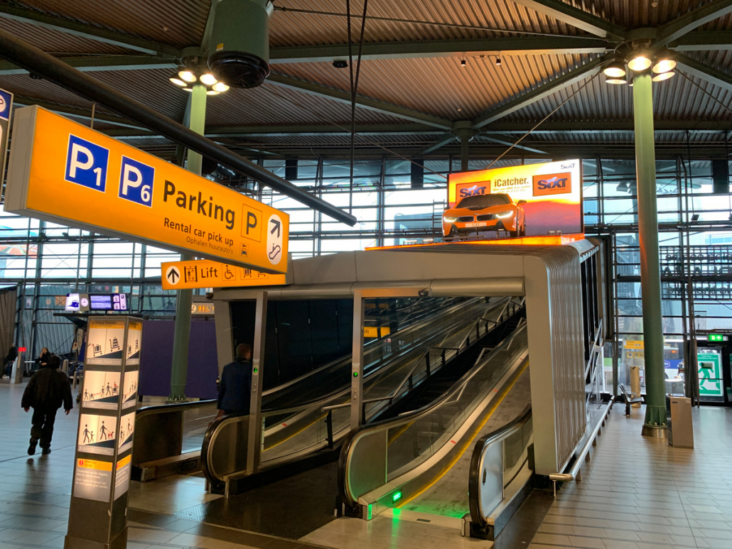 Escalator to the rental car pickup area at Amsterdam Schiphol airport
