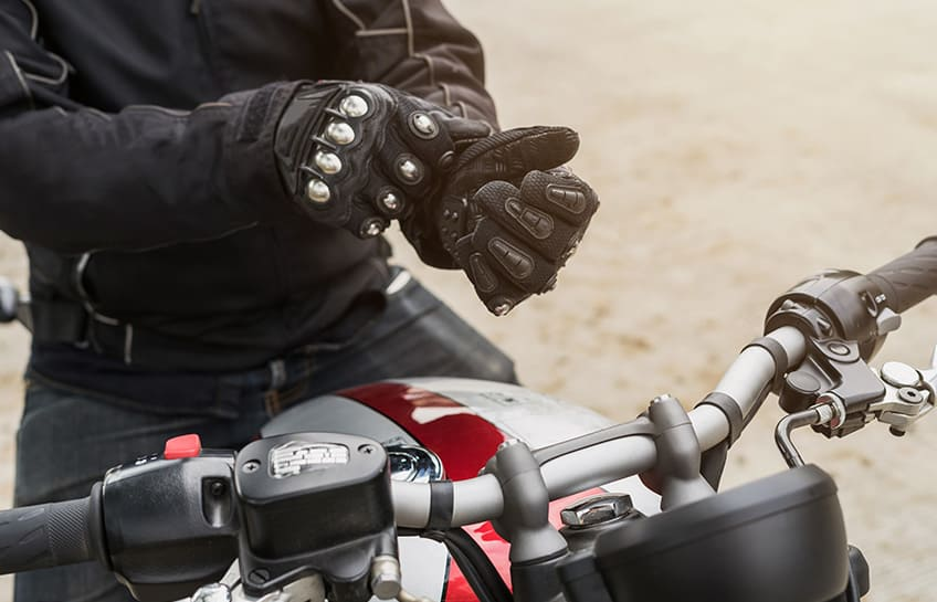 Motorcycle courier sitting on his bike putting gloves on