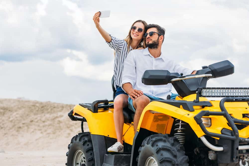Young couple taking selfie while sitting on quad bike