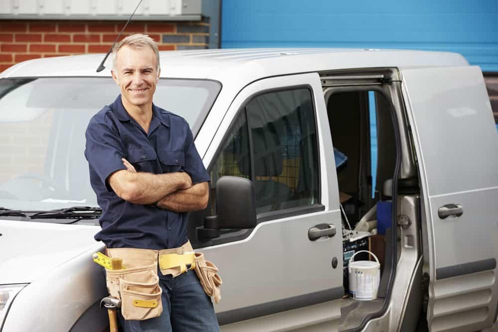 Tradesman standing with the van he has borrowed