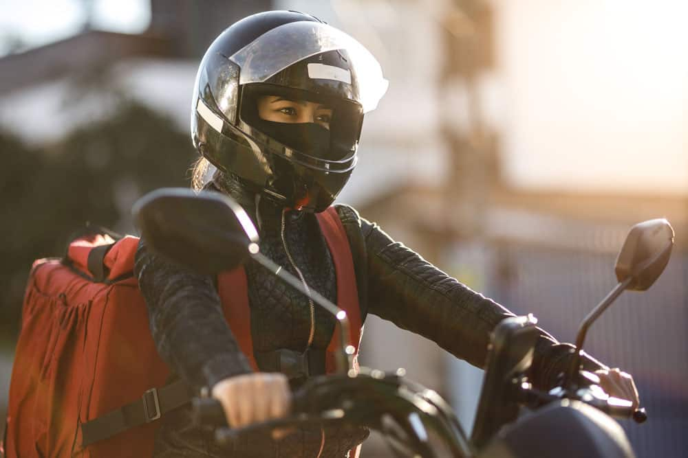 Female motorcycle courier out making deliveries.