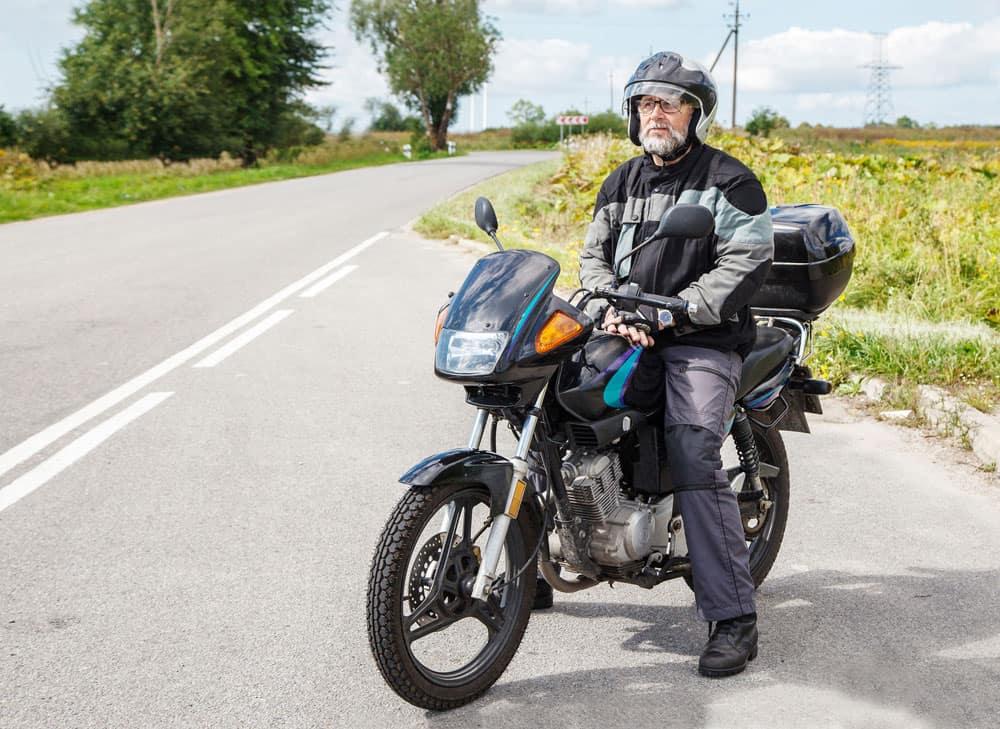 Man on motorbike wearing an open face helmet