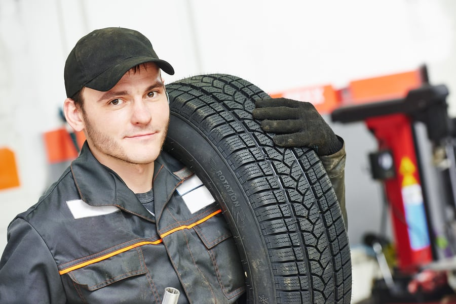 Tyre fitter ready to fit new tyre on a car