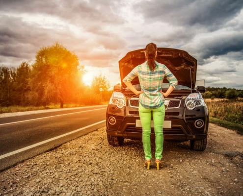 Woman in front of broken down car