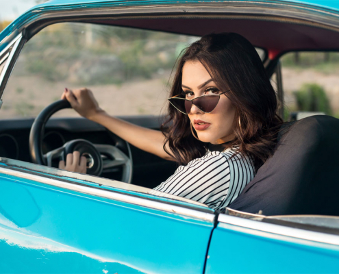 Woman wearing sunglasses driving car with windows down