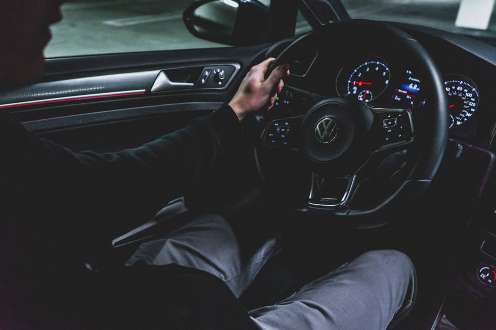Man driving VW car in the dark. Dashboard is lit.