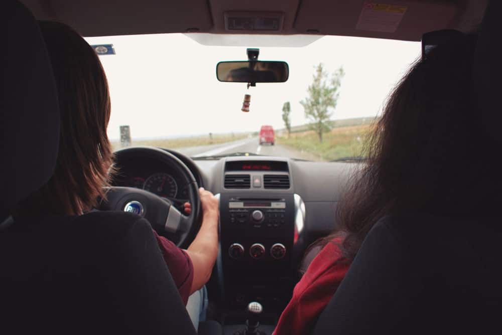 Woman driving Fiat car.